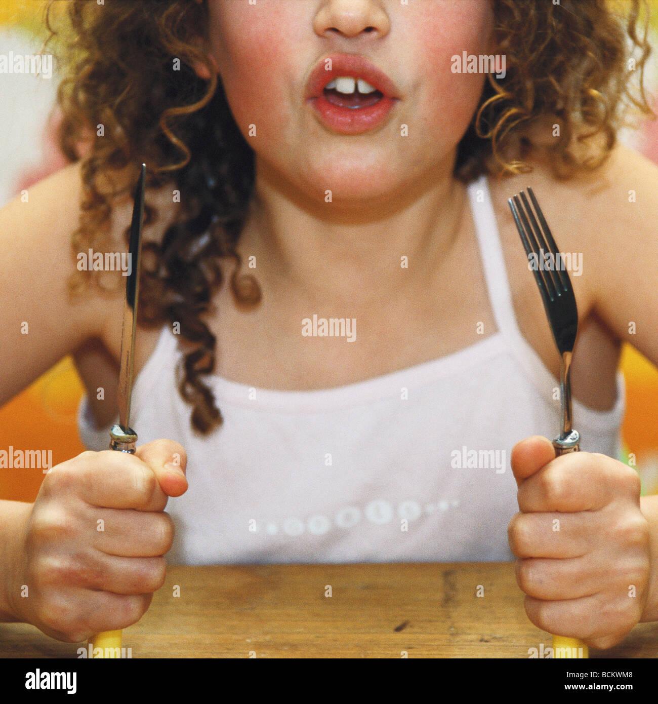 Mädchen mit Messer und Gabel, Mund öffnen Stockbild