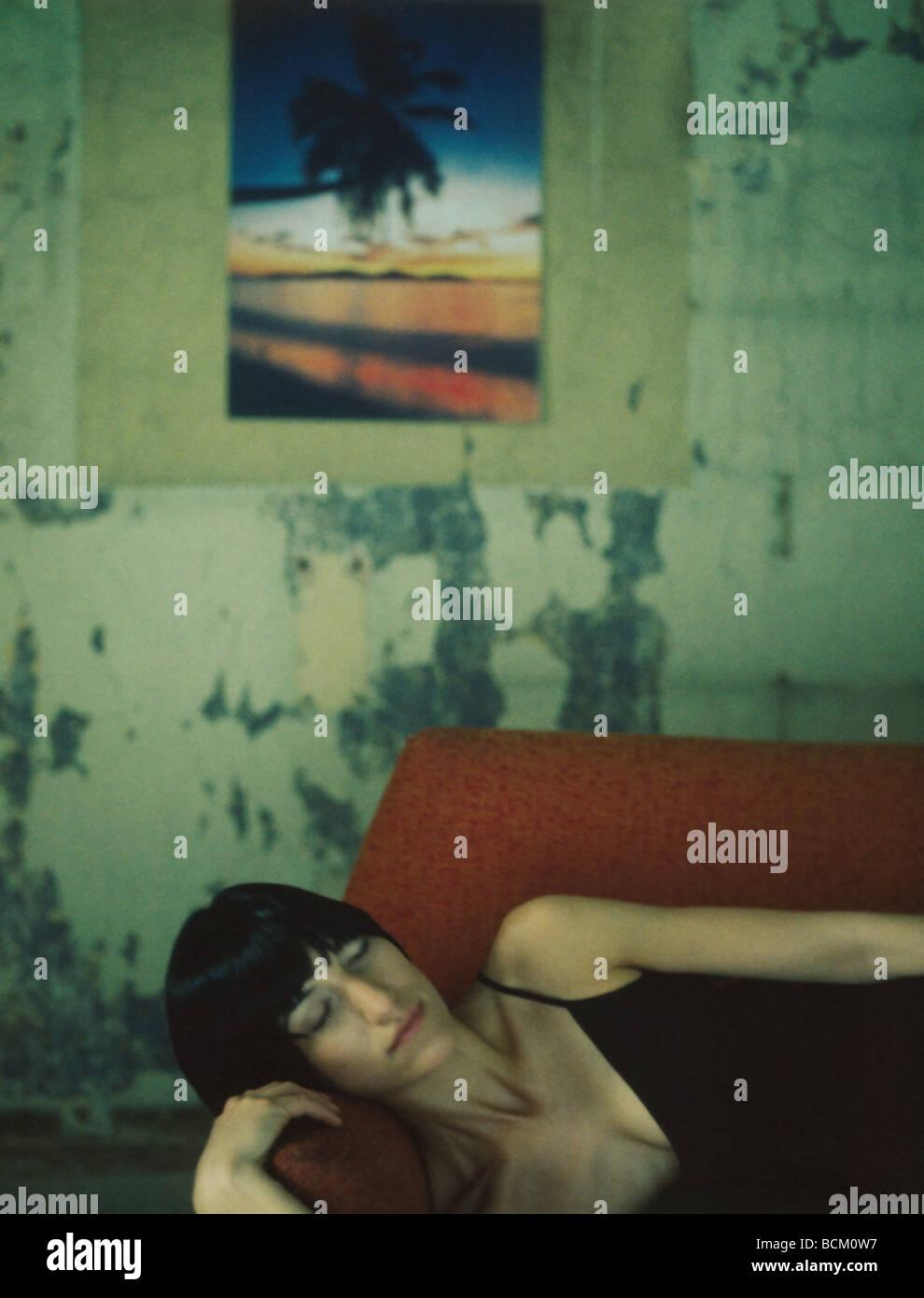 Frau auf Sofa liegend mit geschlossenen Augen, Farbfoto auf Wand im Hintergrund Stockbild