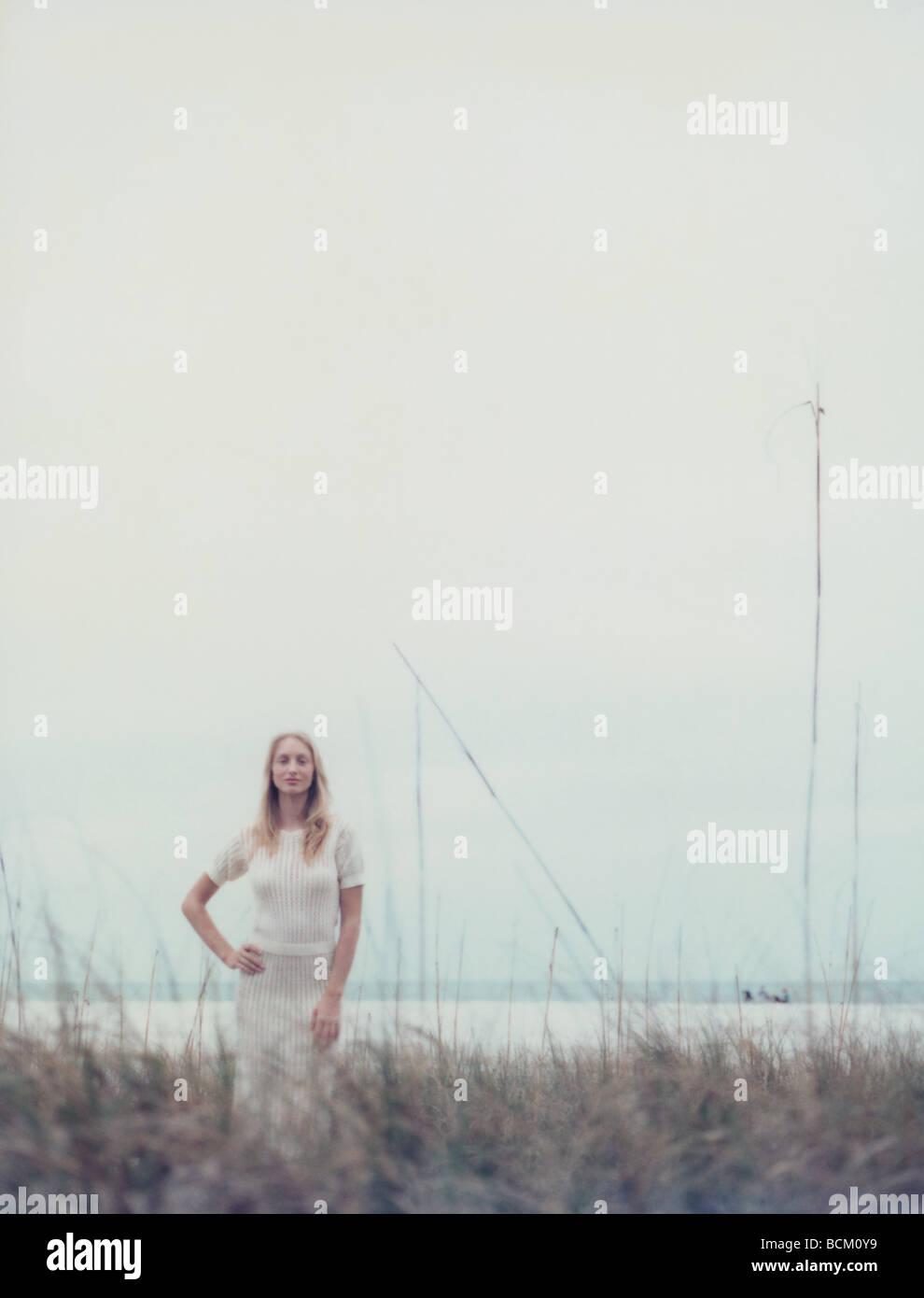 Junge Frau im Kleid am Strand mit Hand auf Hüfte, Dünengras im unscharfen Vordergrund stehend Stockbild
