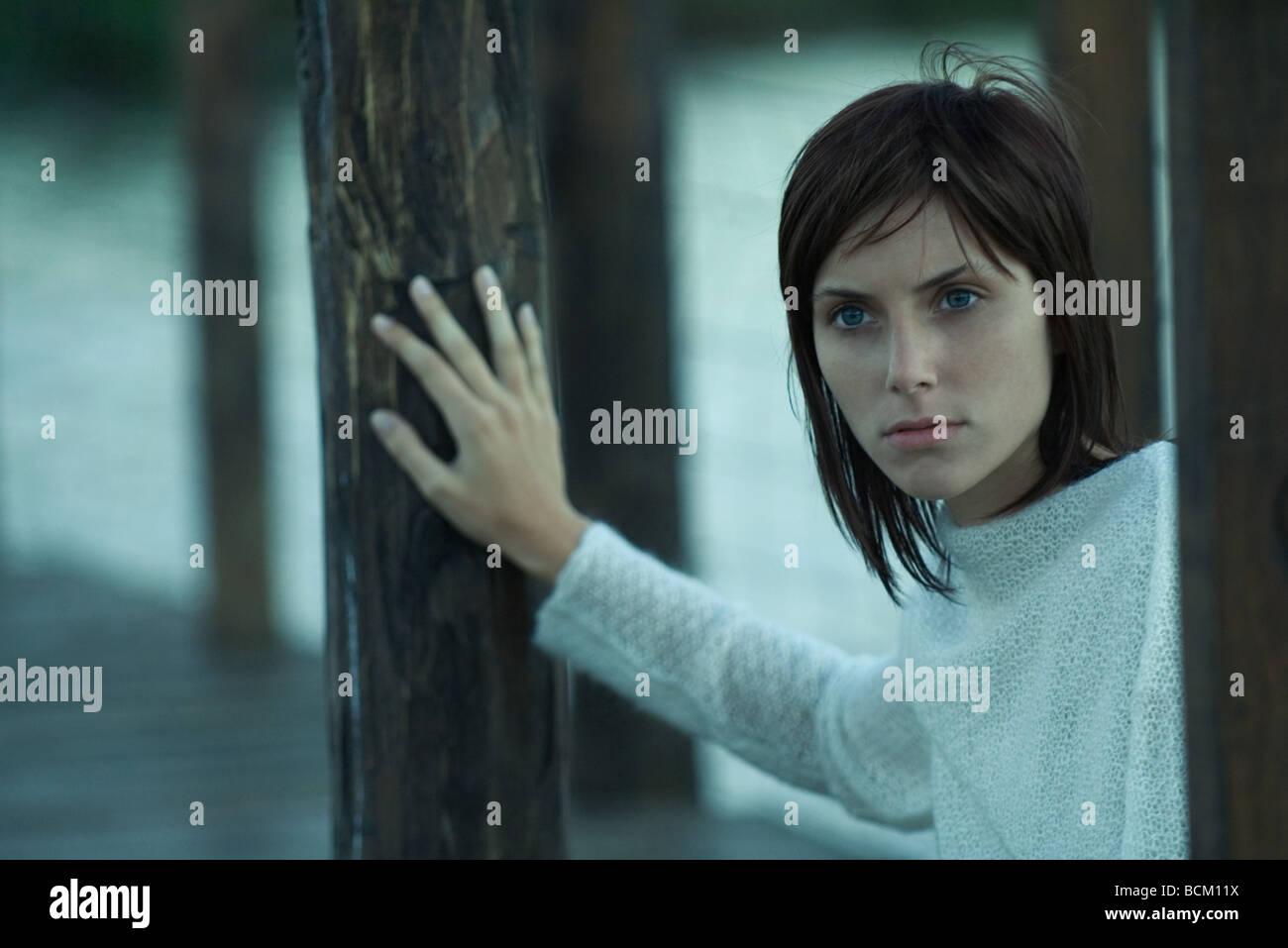Frau am Pier, wegsehen, Kopf und Schultern an Holzpfosten gelehnt Stockbild