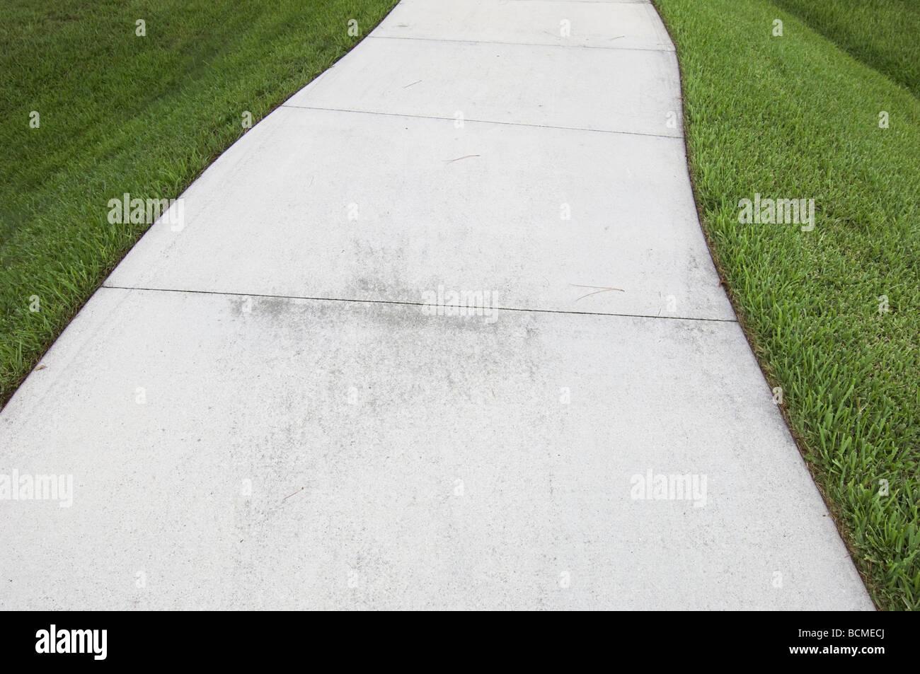 gebogene Bürgersteig durch Rasen Stockbild