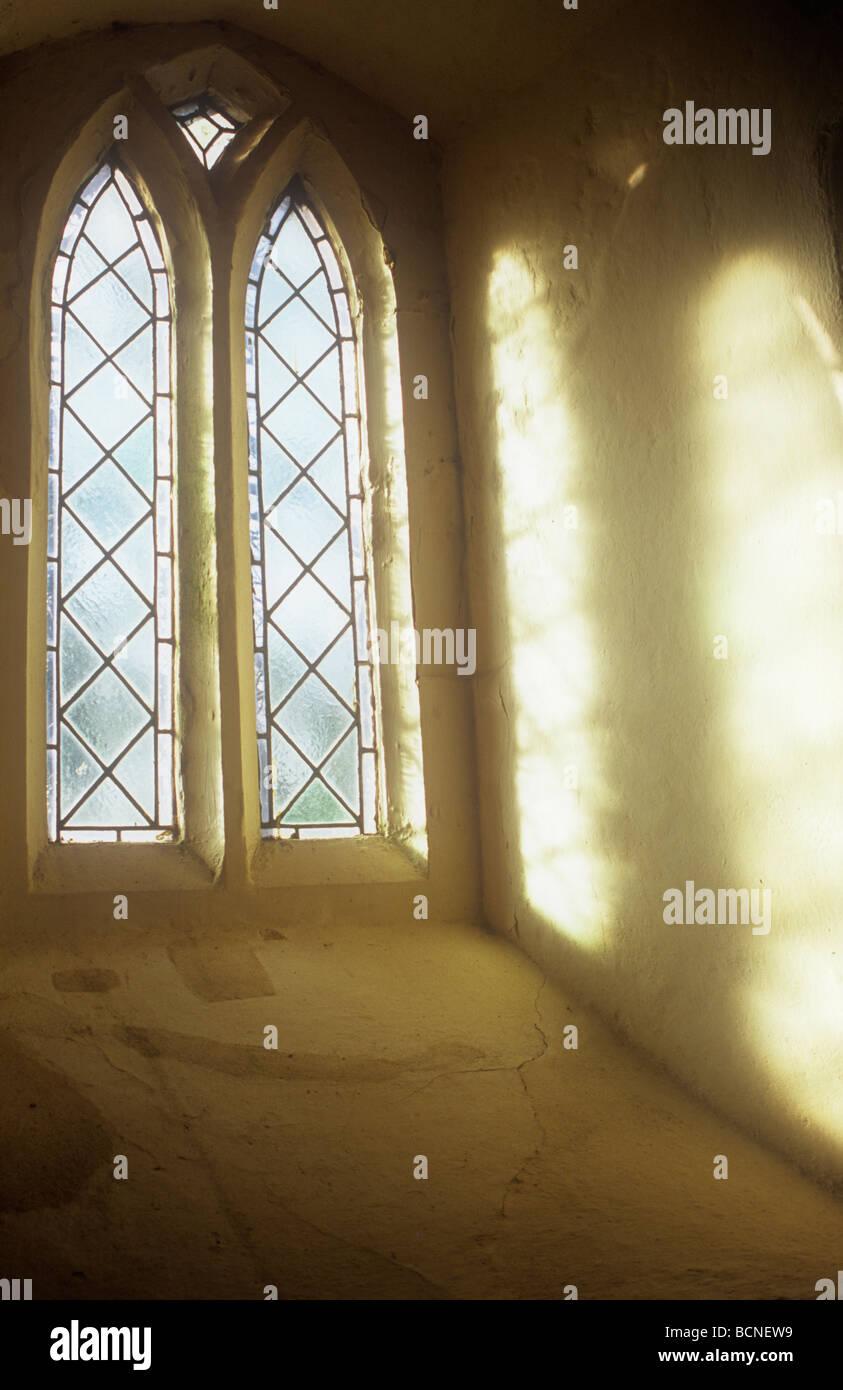 Weiches Licht strömt durch zwei aufrechte mattierte Diamant Bleiglasfenster und projiziert Creme Wand Tiefe Stockbild