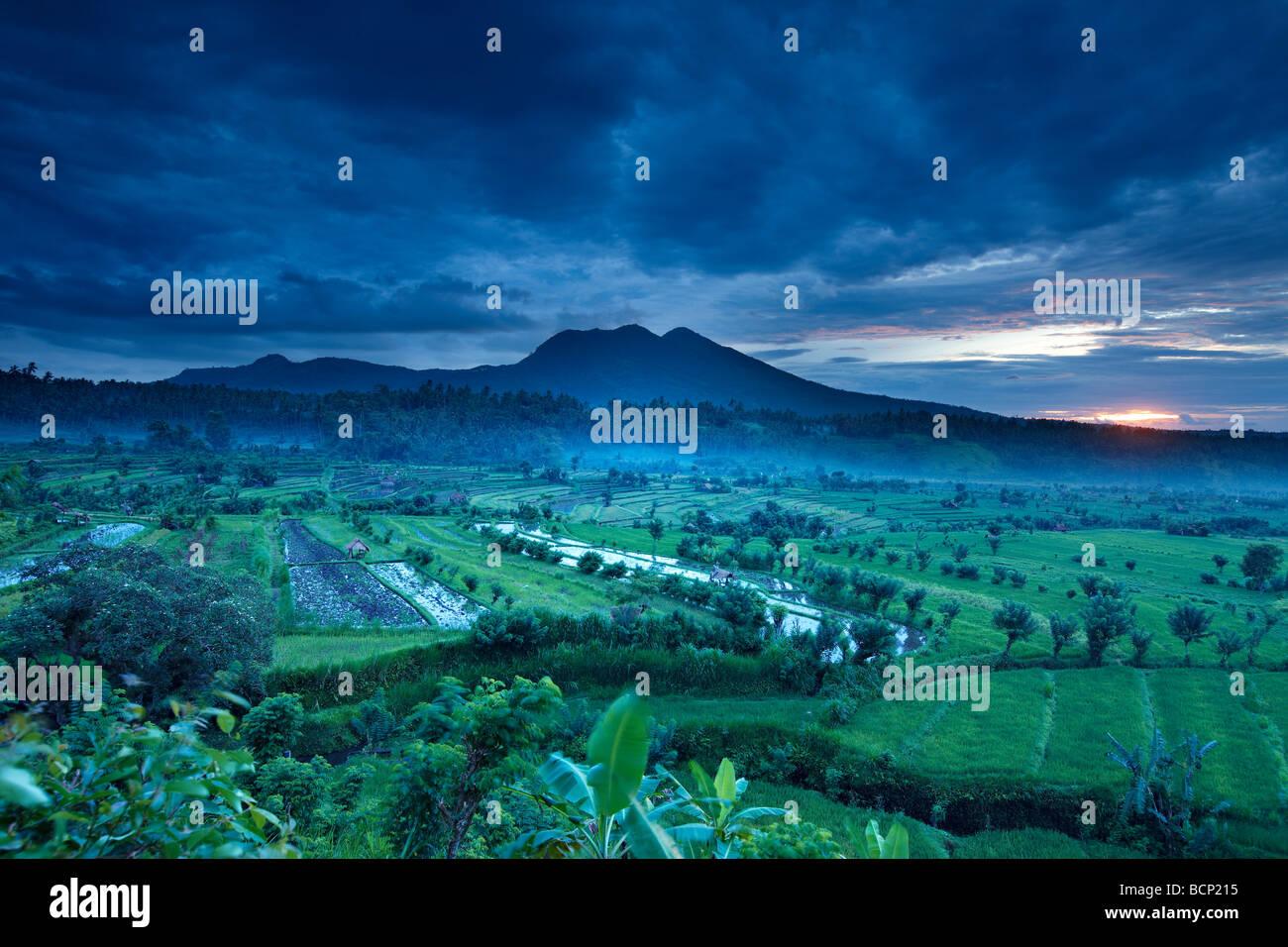 terrassierte Reisfelder in der Nähe von Tirtagangga im Morgengrauen mit der Sonne steigt über die vulkanische Gipfel Stockfoto