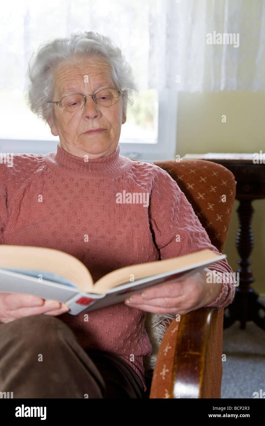 Frau in Ihren Siebzigern Sitzt in Einem Sessel Und liest in Einem Buch Stockbild