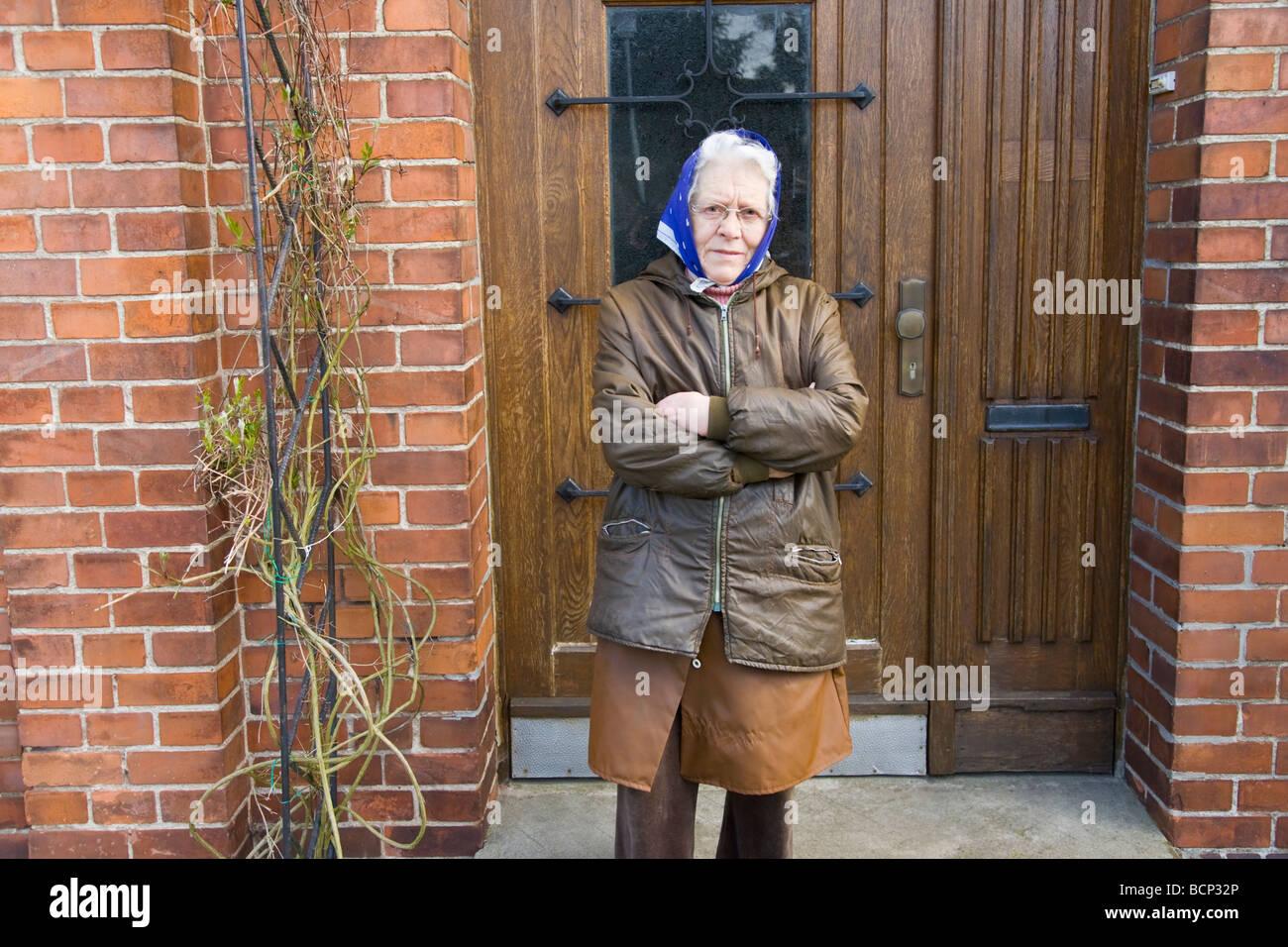 Frau in Ihren Siebzigern Mit Kopftuch Steht Mit Verschränkten Armen Vor Ihrer Haustür Stockbild