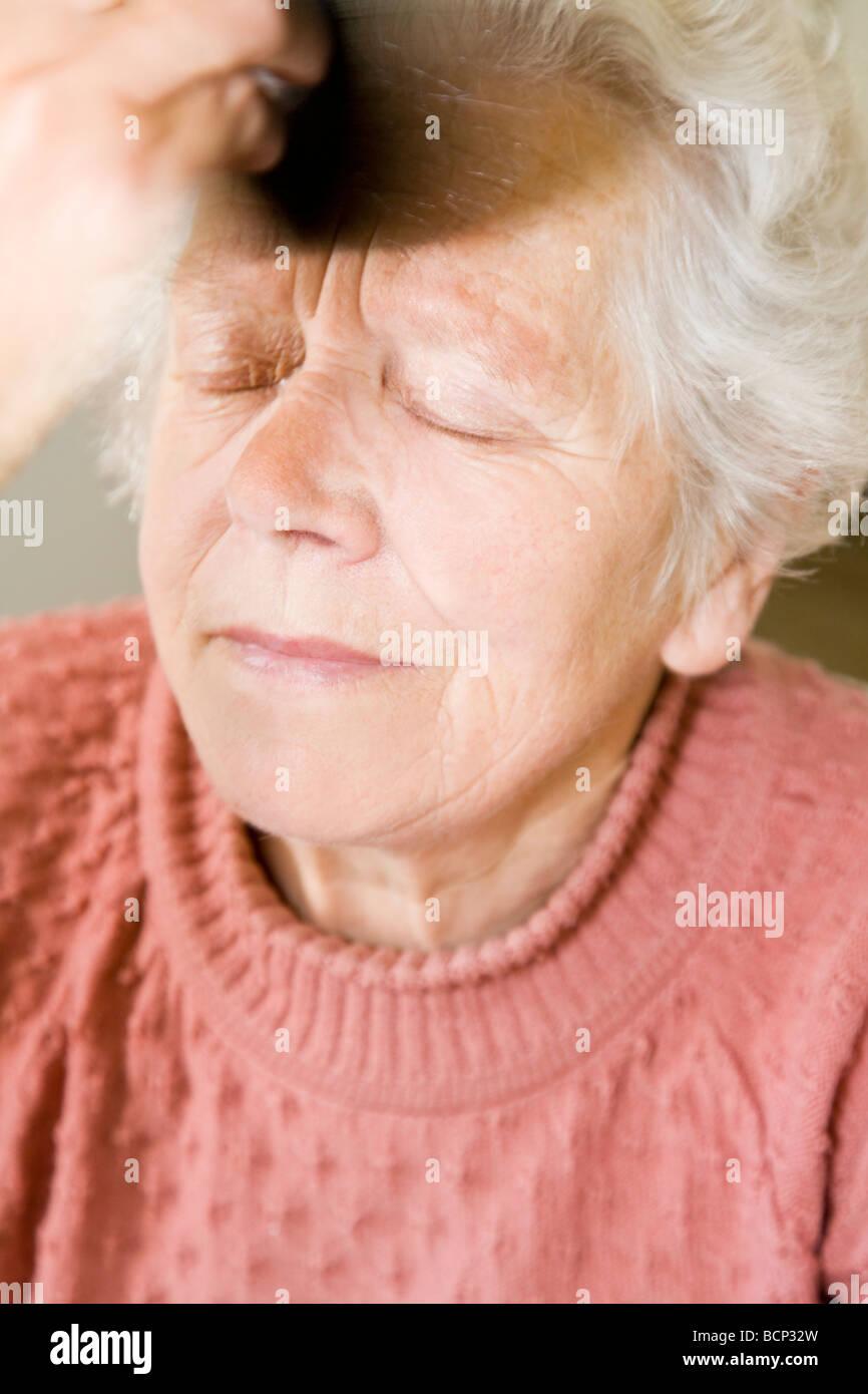 Frau in Ihren Siebzigern feststeht Sitsch Im sich pudern Stockbild