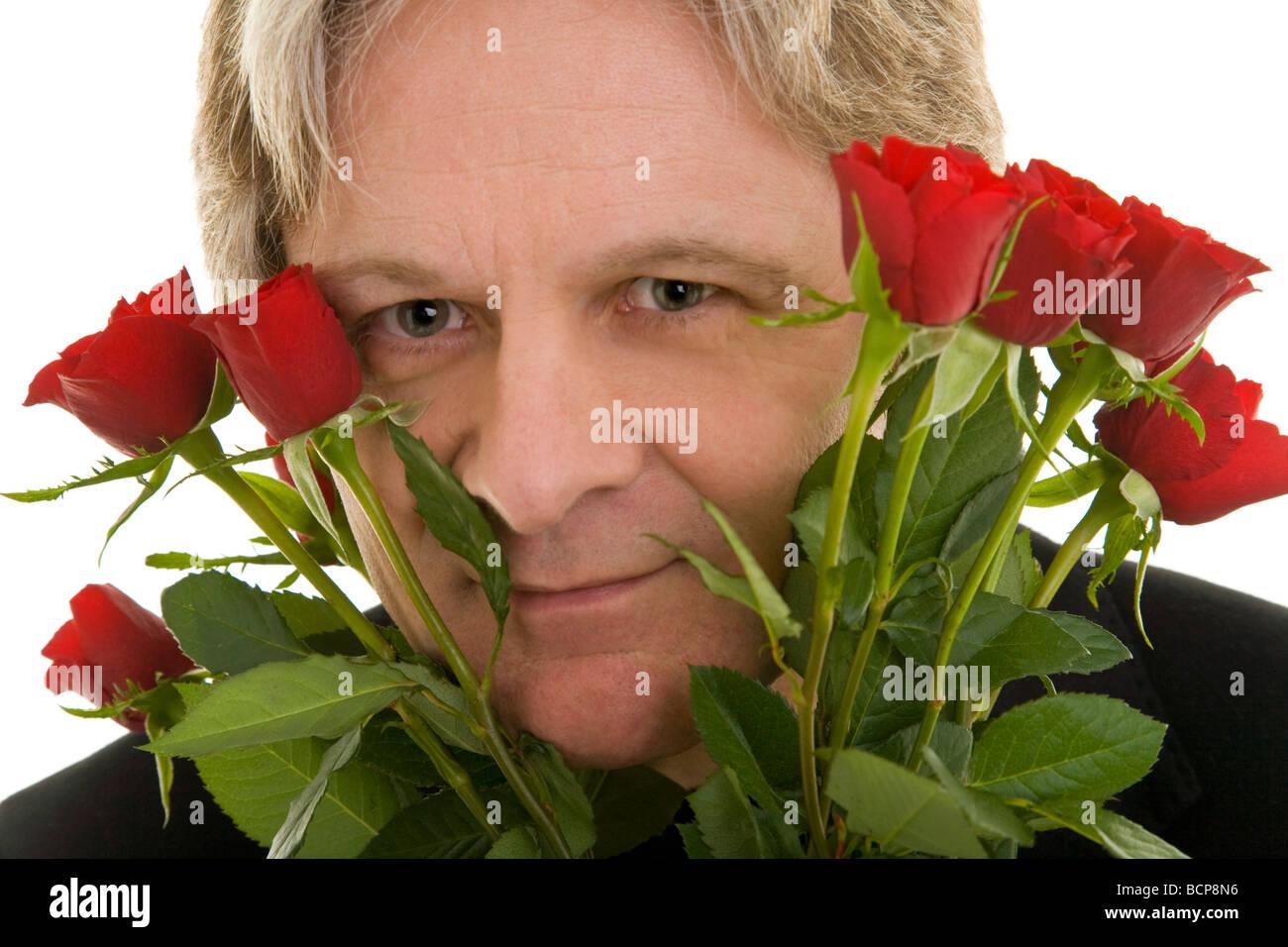 Mann Schaut Durch Einen Strauß Roter Rosen Stockbild