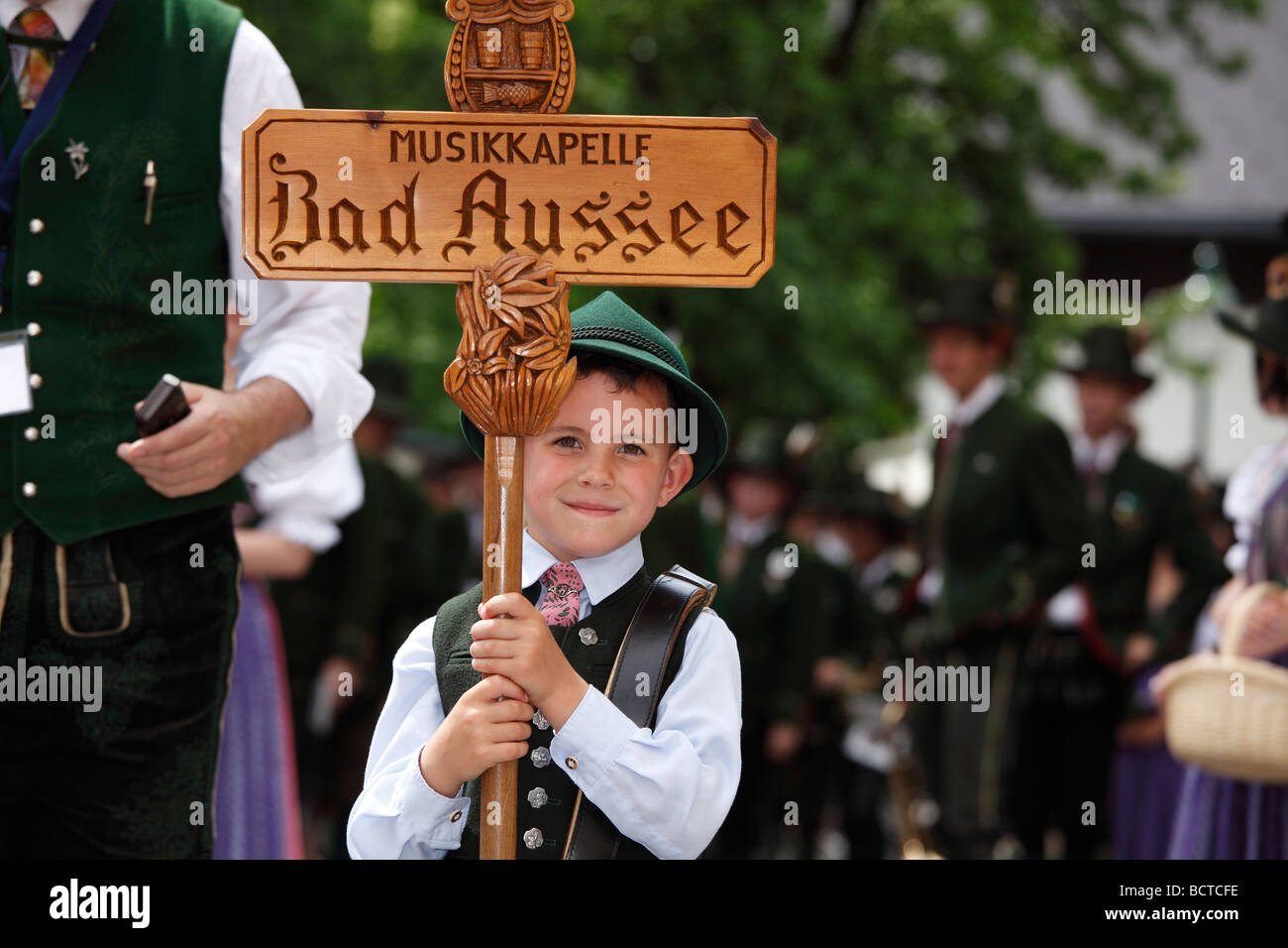 """Junge in traditioneller Tracht mit hölzernen Schild """"Musikkapelle Bad Aussee"""" """"Band Bad Aussee"""" Stockbild"""