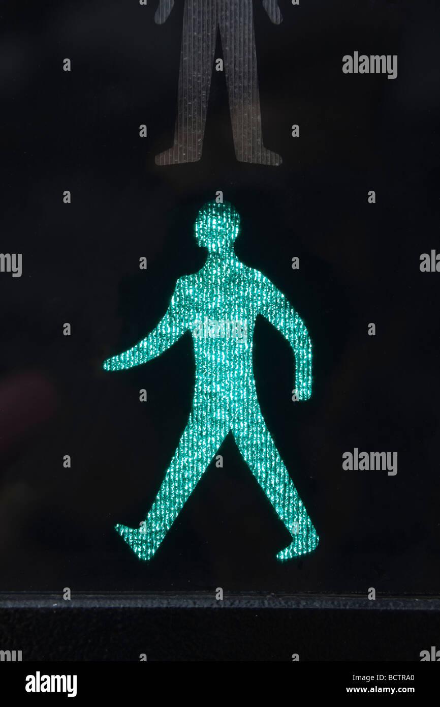 Nahaufnahme von beleuchteten Fuß Grüner Mann sicher zu überqueren Straße Symbol auf einem Fußgängerüberweg Stockbild