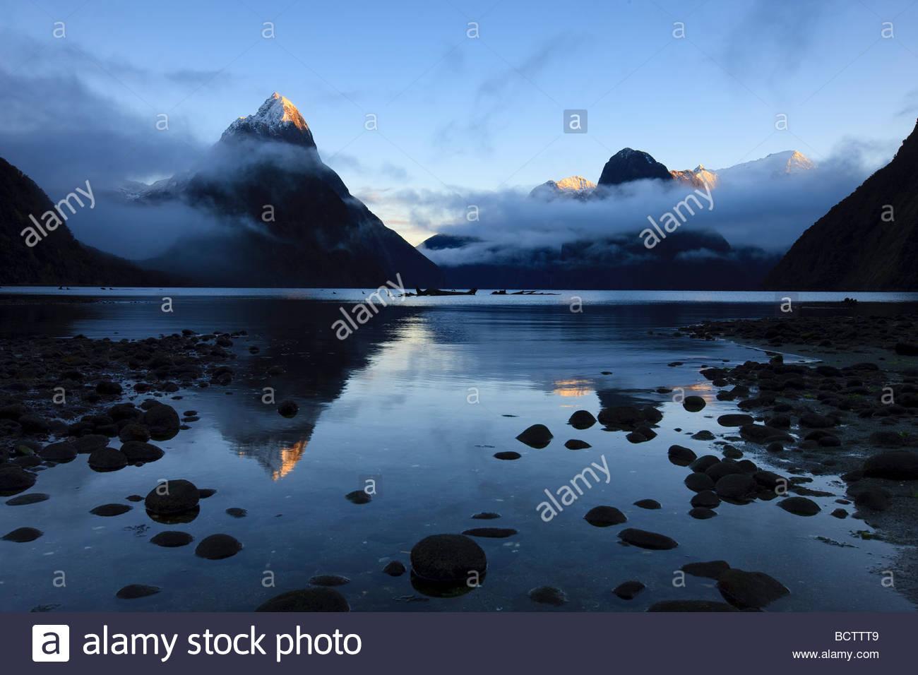 Mitre Peak, Mount Pembroke und andere Berge im Fjordland National Park, New Zealand, spiegeln sich in Milford Sound. Stockbild