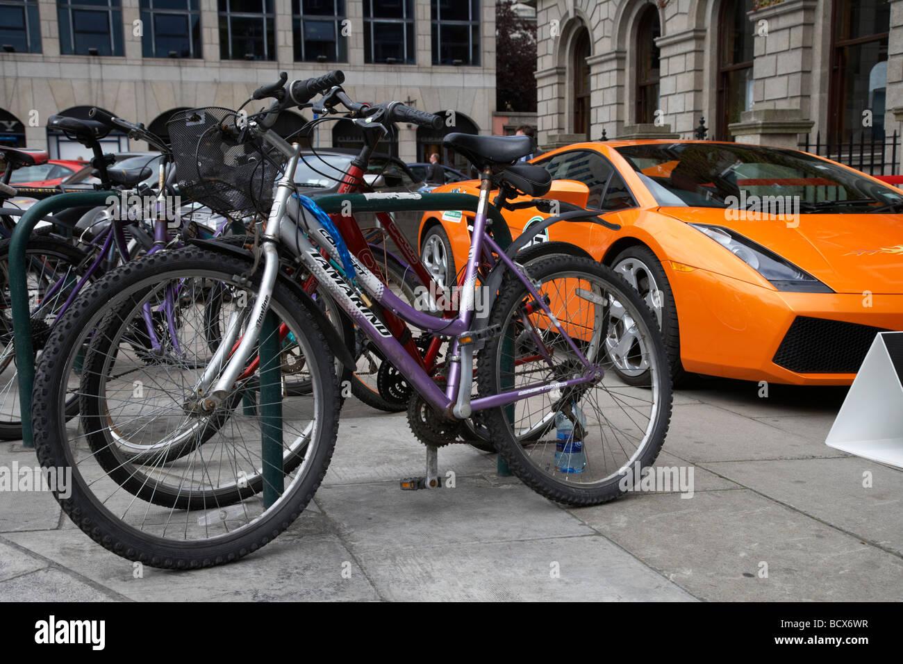 Lamborghini Sportwagen geparkt auf Bürgersteig neben Reihe Fahrräder Dublin, Republik Irland Stockbild
