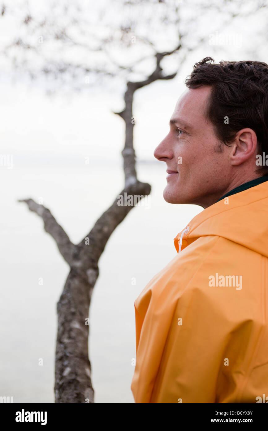 Mann im Regenmantel, Blick auf einen See Stockbild