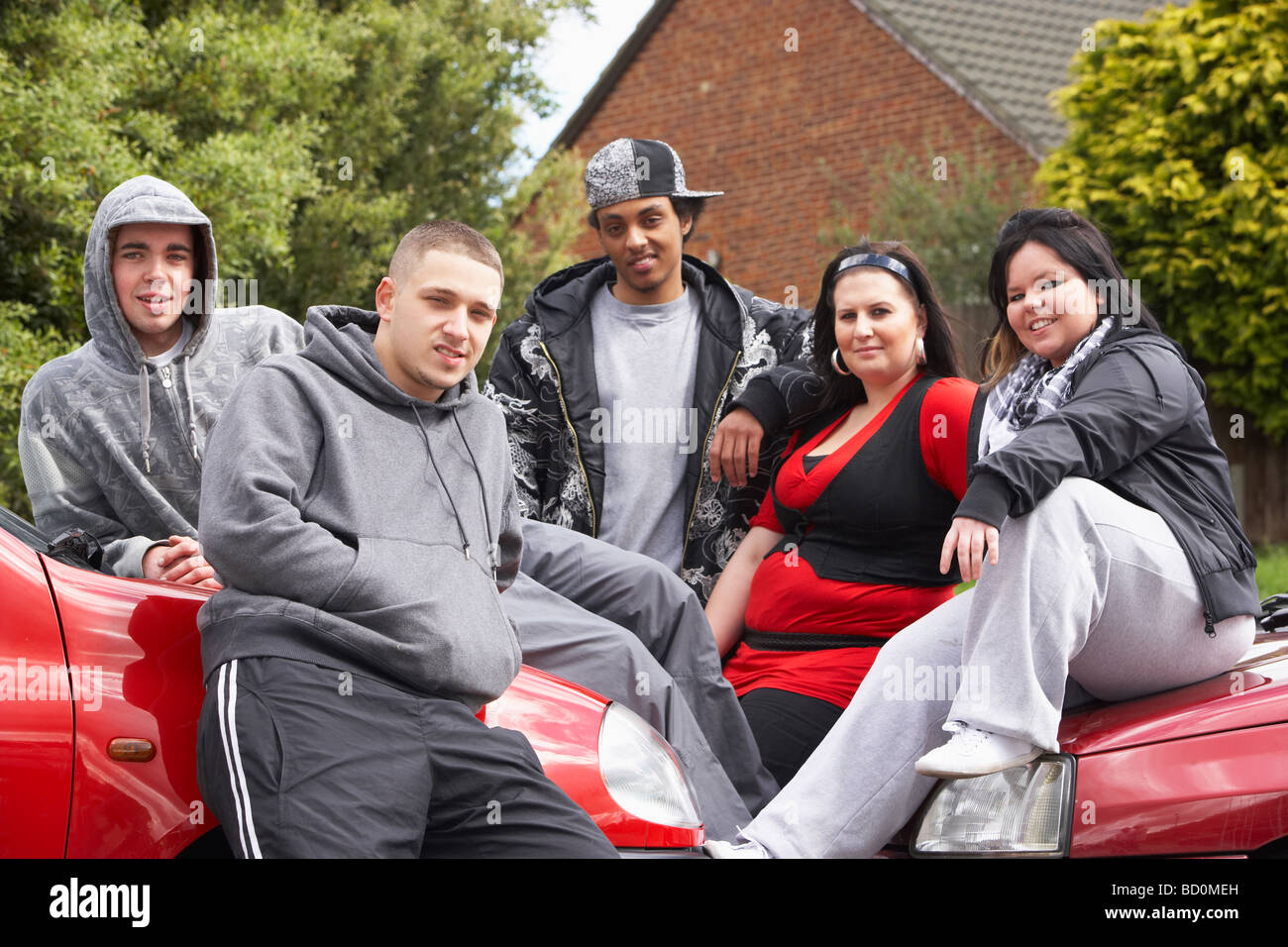 Bande von Jugendlichen sitzen auf Autos Stockbild