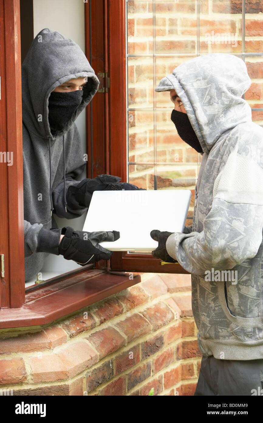 Junge Männer brechen in Haus Stockfoto