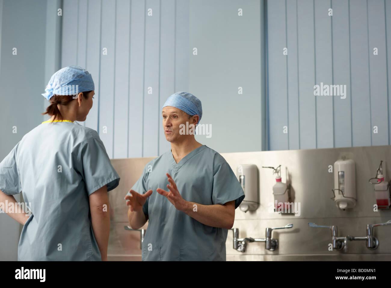 Medizinisches Personal in Scrubs in Diskussion Stockbild