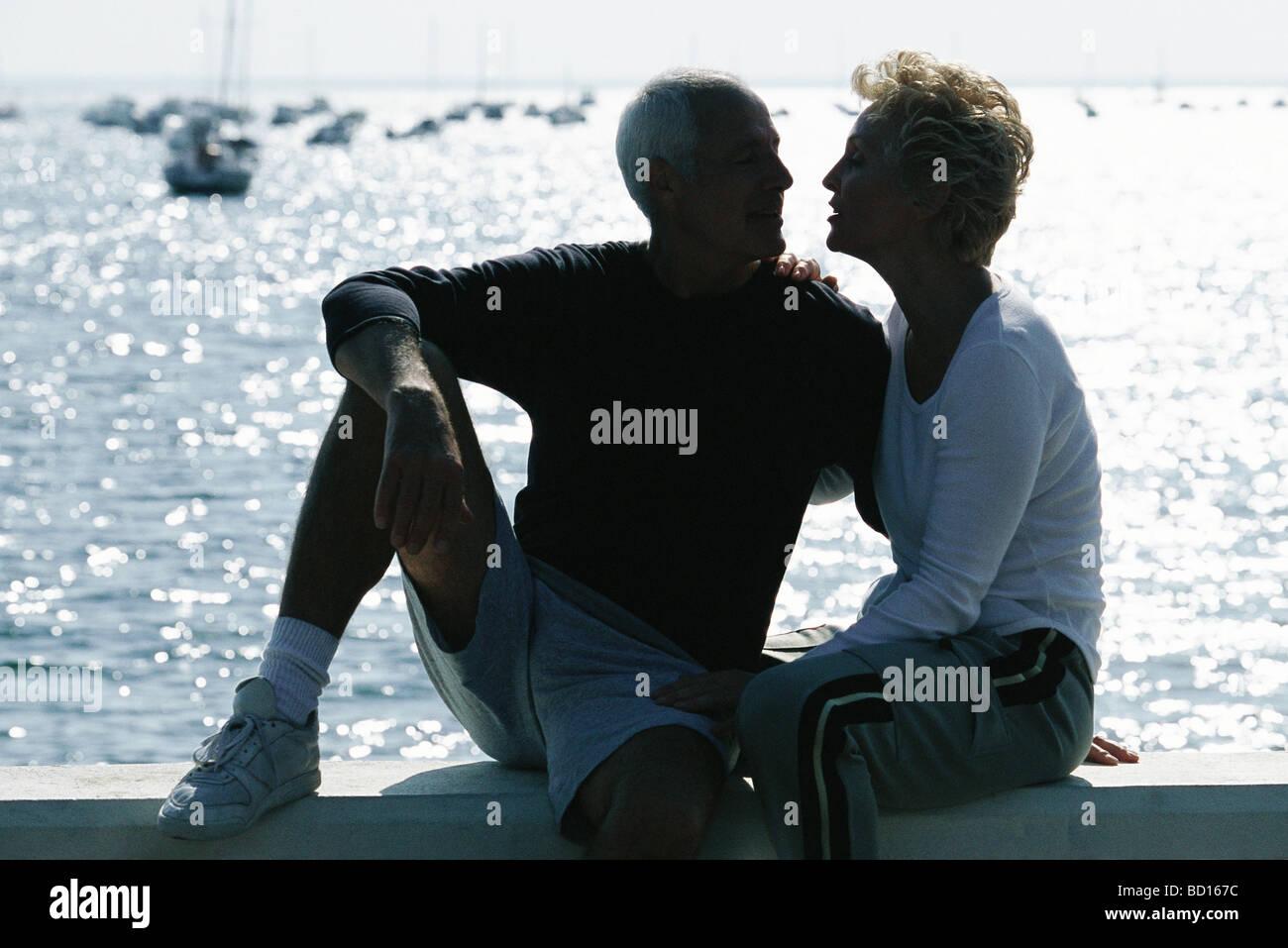 Älteres paar sitzen zusammen auf Pier, Hintergrundbeleuchtung Stockbild
