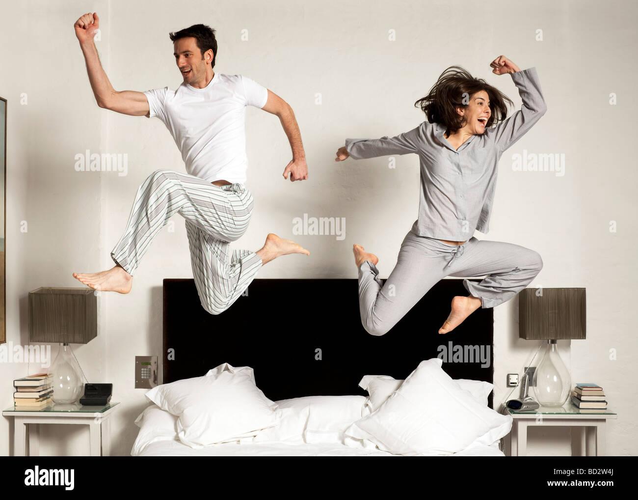 paar aus dem Bett springen Stockbild