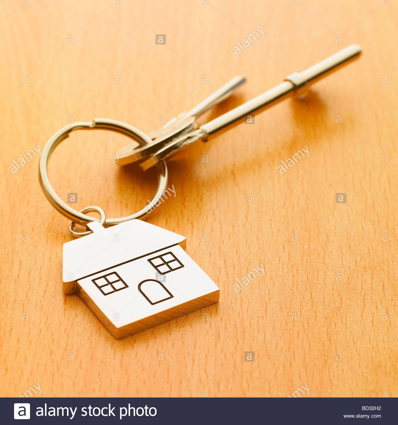 Hausschlüssel an einem Haus geprägt Schlüsselanhänger auf Tischplatte befestigt. Stockbild