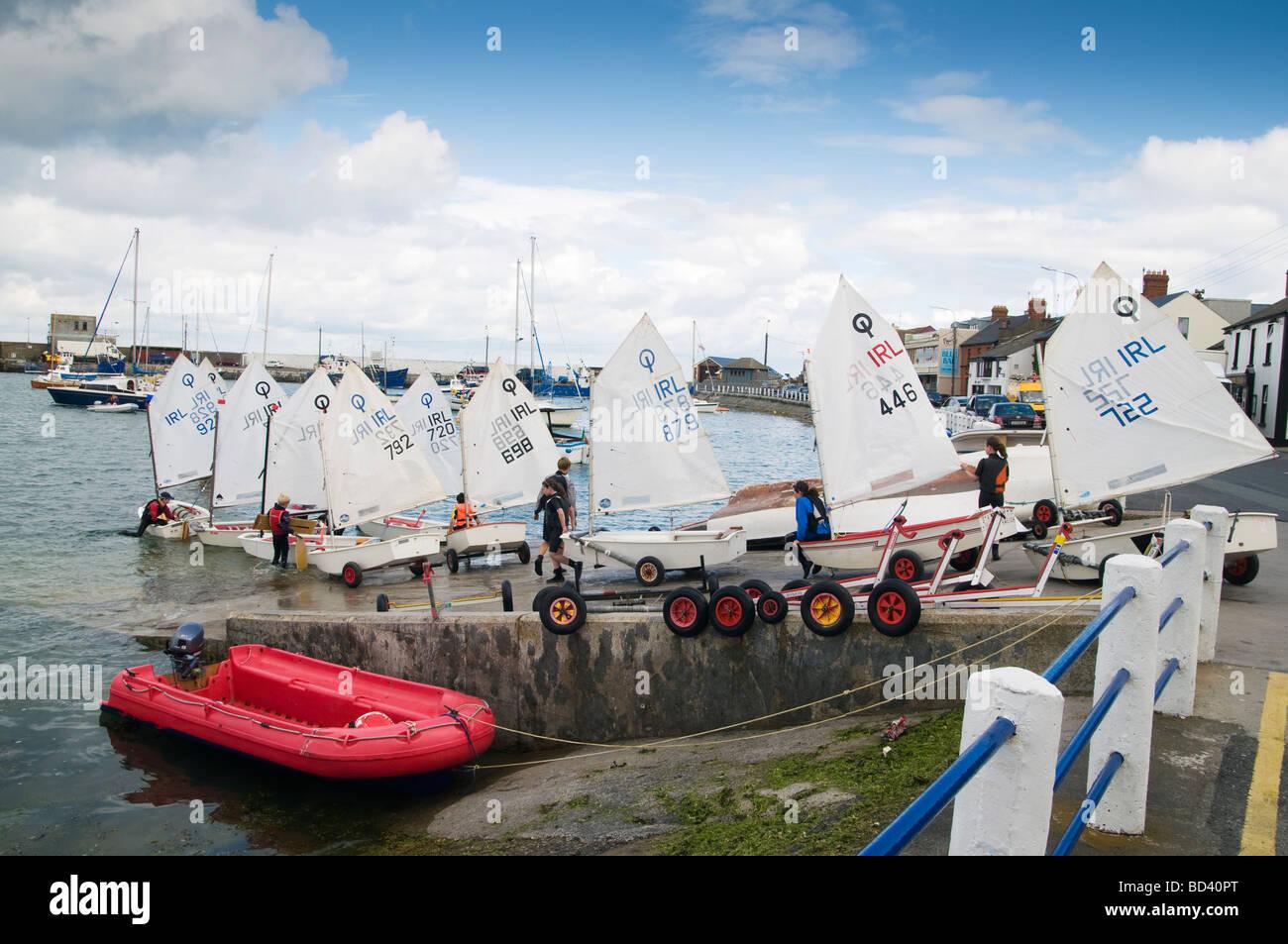 Kinder starten ihre Optimist Segeljollen an der Slipanlage in Skerries Hafen North County Dublin Irland Stockbild