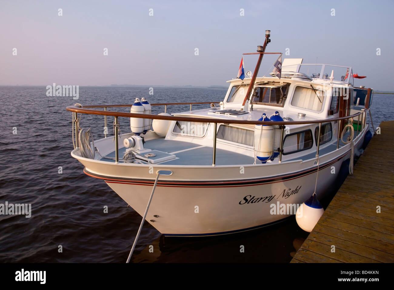 Ein Motorboot liegt an einem hölzernen Bootssteg am Lauwersmeer Stockbild