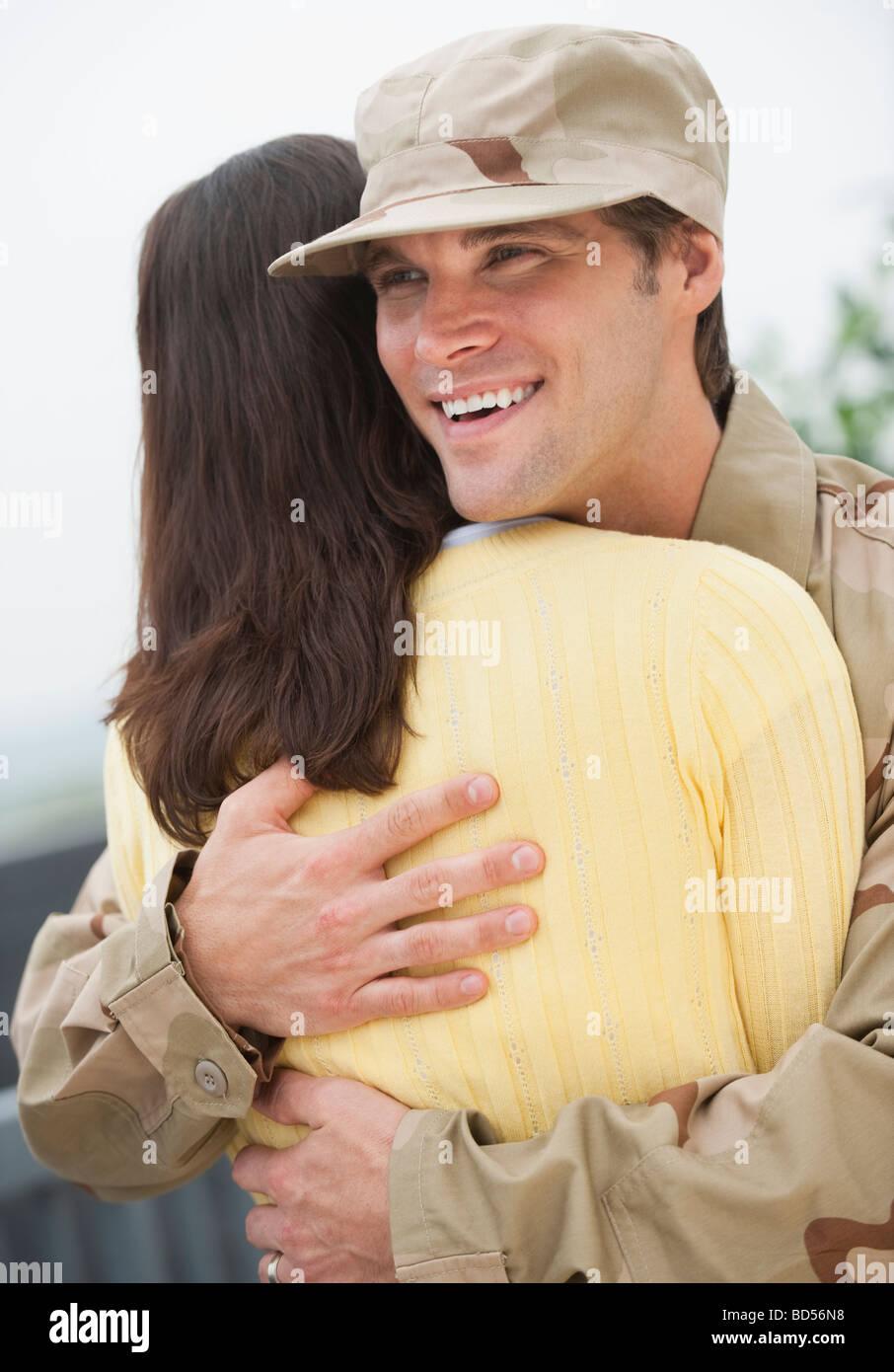 Eine Frau umarmt einen militärischen Offizier Stockbild