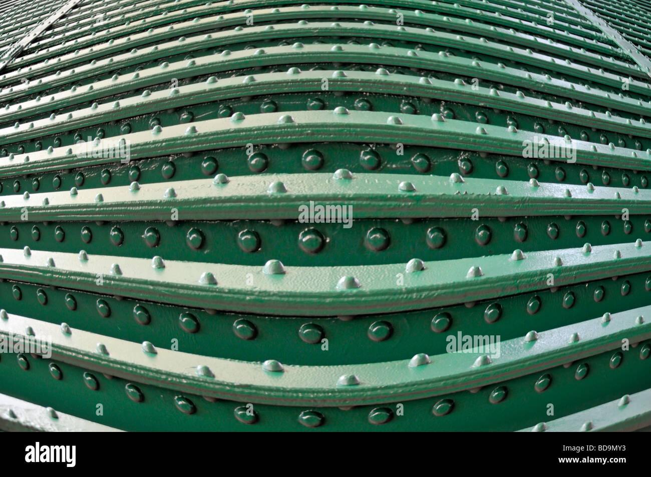 Nieten & Nietenköpfe in Stahlträgerkonstruktion auf der Unterseite der Eisenbahnbrücke closeup als Muster abstrakt Stockfoto