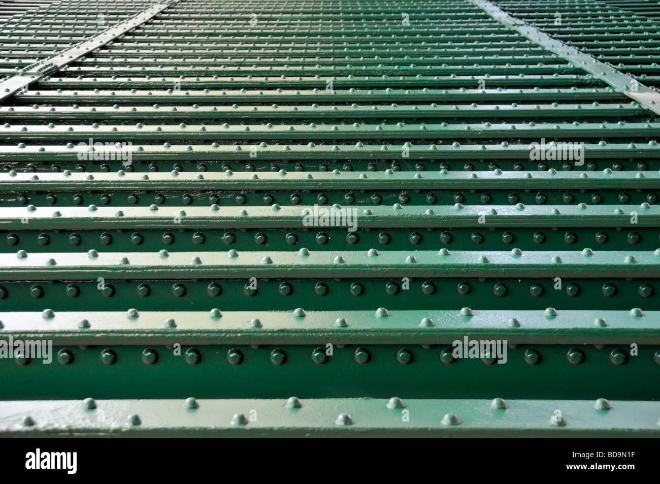 Linien von Nieten in Stahlträger auf Unterseite der Eisenbahn Brücke über Fluß nahe bis invertiert Stockfoto