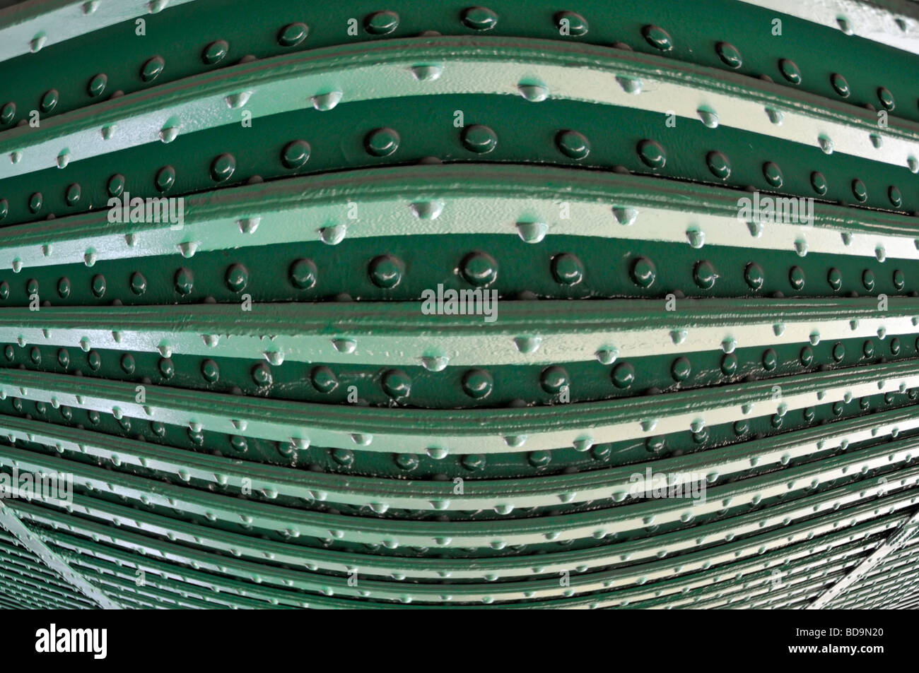 Nieten in Stahlträger an Unterseite der Eisenbahnbrücke hautnah als Muster abstrakt Hintergrundbild manipuliert Stockbild