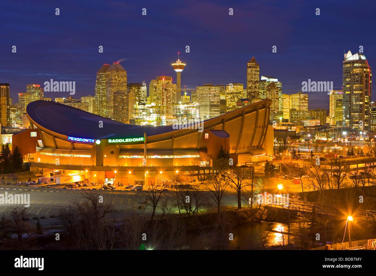 Der Saddledome mit Hochhäusern und dem Calgary Tower im Hintergrund in der Abenddämmerung Stadt von Calgary Stockbild