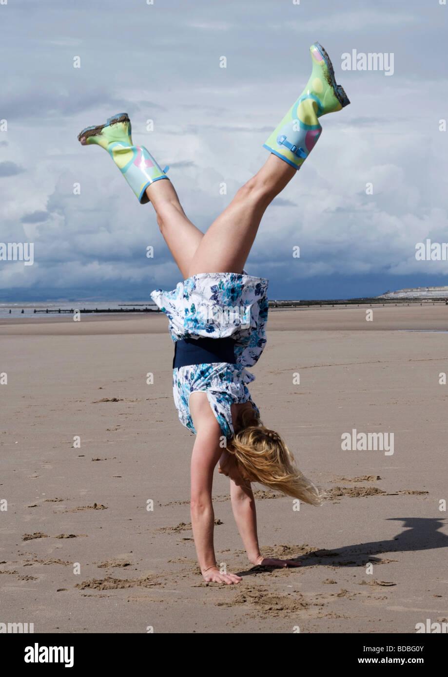 Frau trägt eine altmodische Blumen Kleid und Wellington Stiefel, macht einen Handstand am Strand Stockbild
