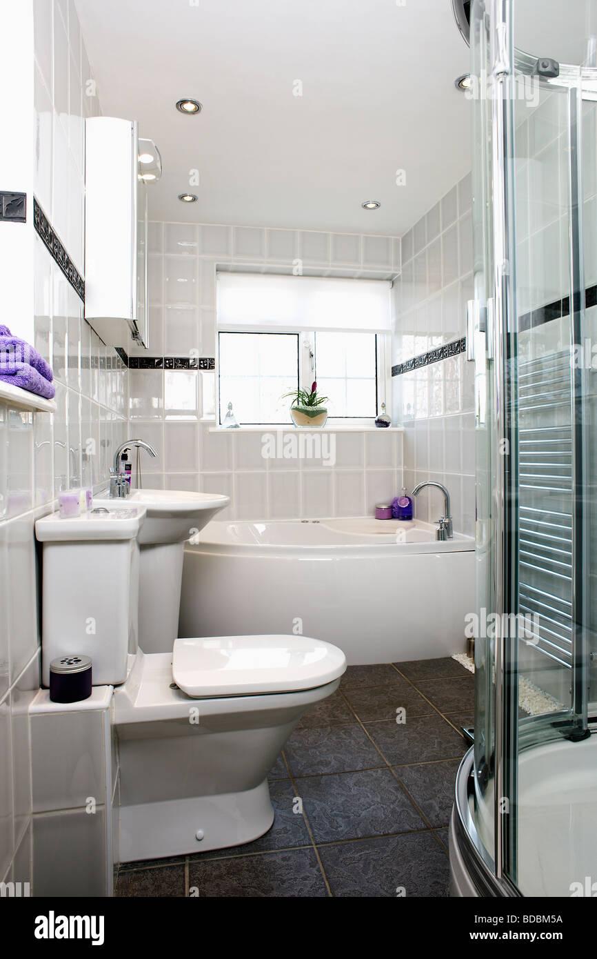 Moderne Grau Geflieste Badezimmer Mit Weissen Toilette Und Badewanne Und Schieferbodenbelag Stockfotografie Alamy