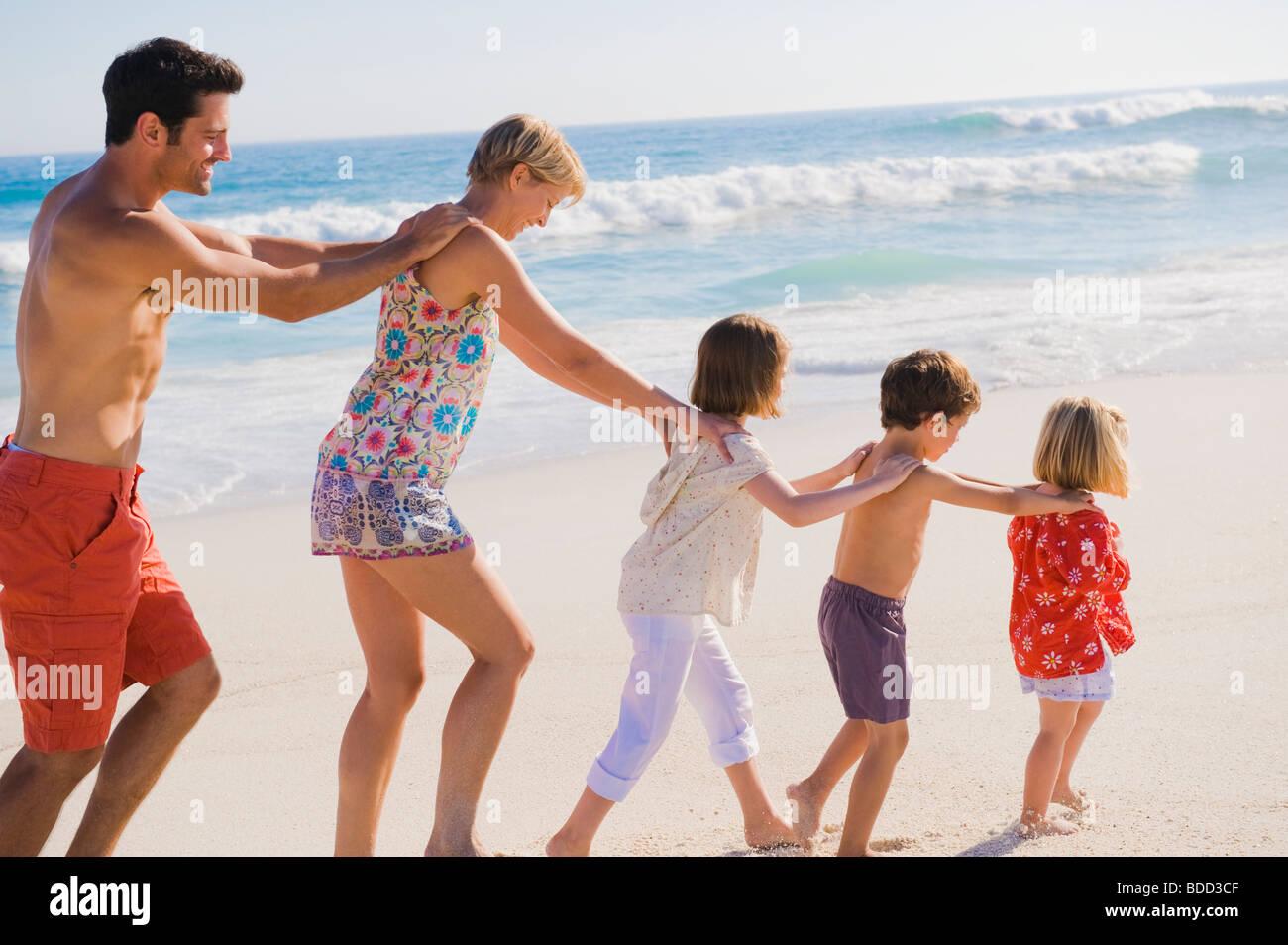 Familie zu Fuß am Strand in Zugbildung Stockfoto