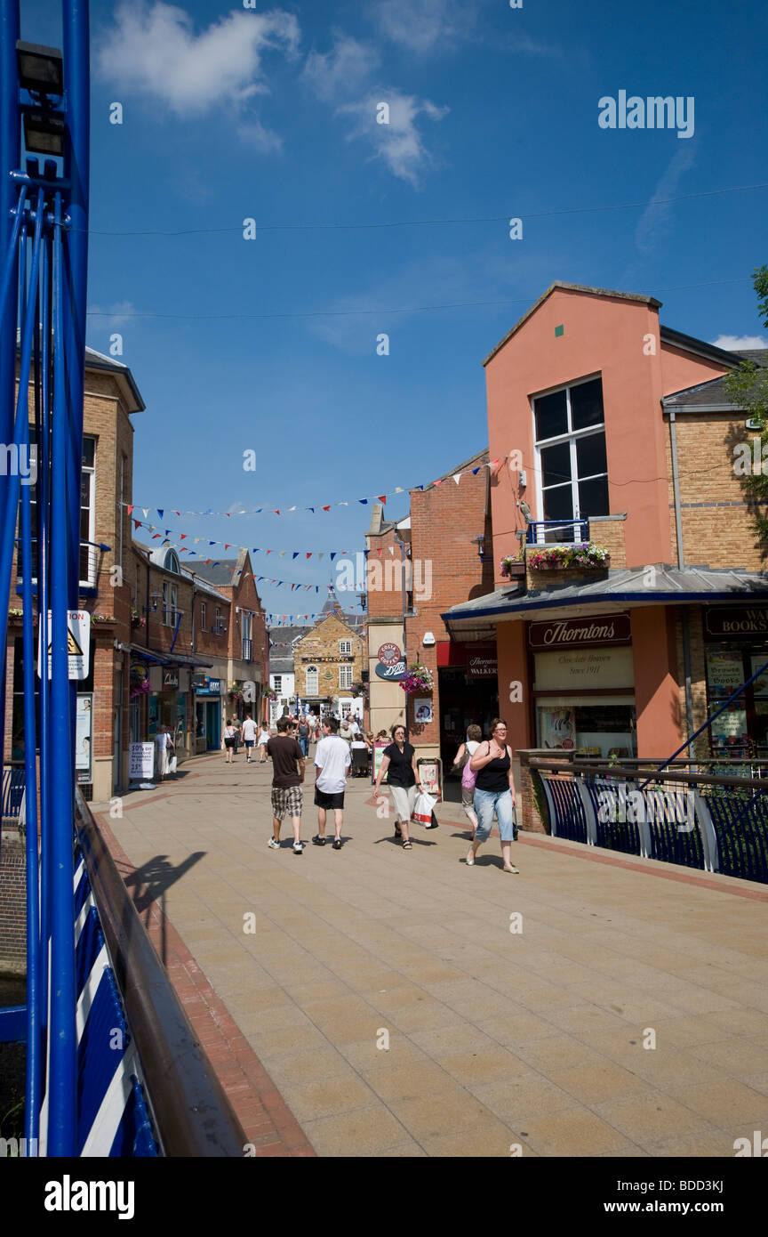Menschen zu Fuß durch eine Fußgängerzone in der hübschen Markt Market Harborough, Leicestershire Stockbild