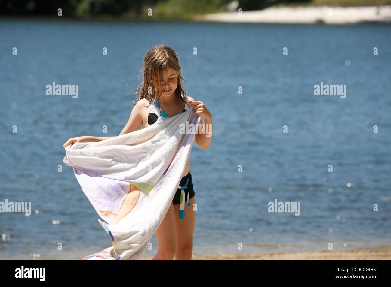 Mädchen mit Handtuch am Strand Stockfoto
