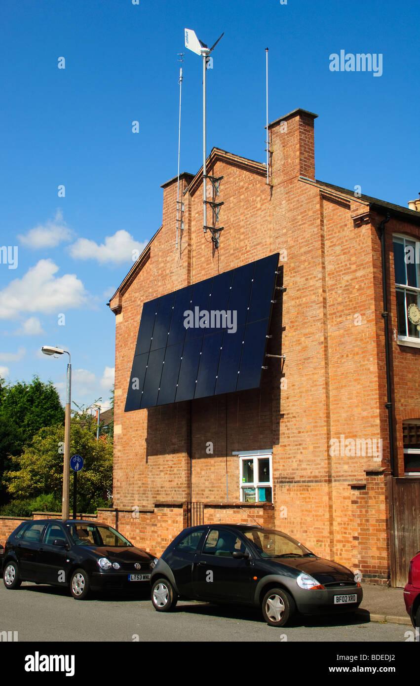 Windgenerator und Sonnenkollektoren angebracht, um die südliche Wand eines Wohnhauses in Leamington Spa, Warwickshire, Stockbild