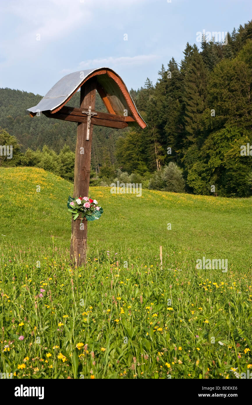 Eine einfache christliche Bildstock, trägt ein Kruzifix und geschmückt mit Blumen, auf einem Feld am Gradisce, Stockbild