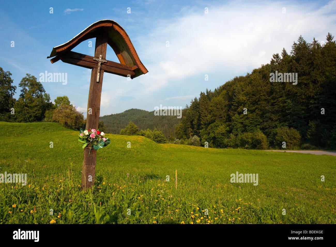 Eine einfache slowenischen Bildstock, trägt ein Kruzifix und geschmückt mit Blumen, auf einem Feld am Stockbild
