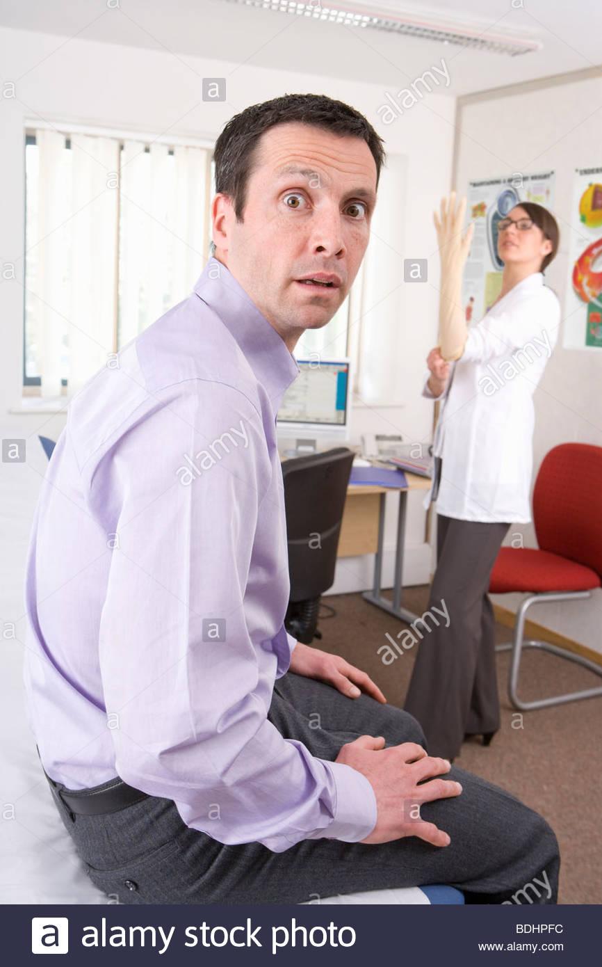 Mann sucht beunruhigt, als Arzt auf OP-Handschuh im Untersuchungsraum setzt Stockbild