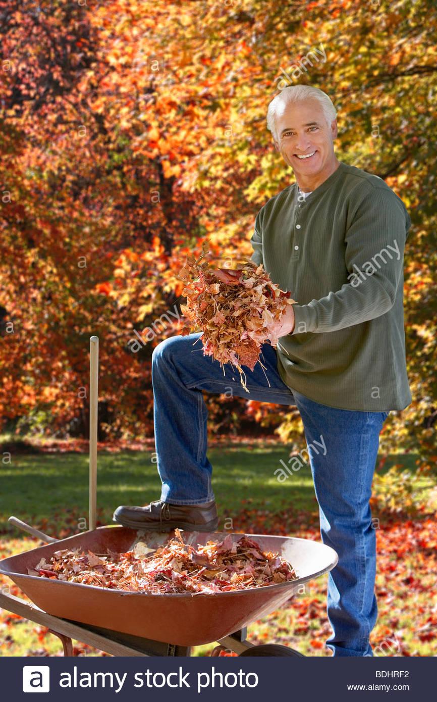 Mann tut Gartenarbeit im Herbst Stockbild