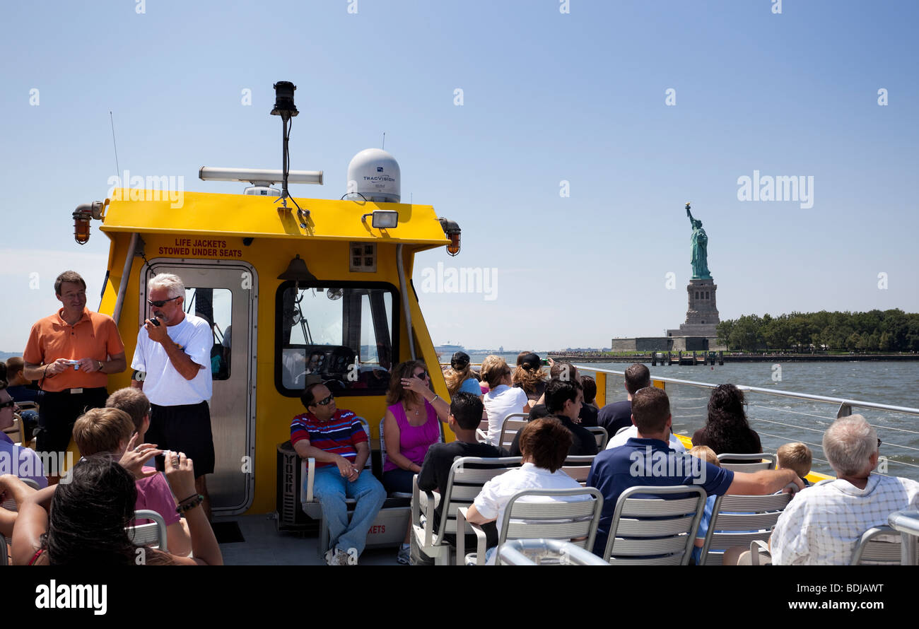 Eine Gruppe von Touristen auf ein Wassertaxi geführte Tour in die Statue of Liberty, Hudson River, New York Stockbild