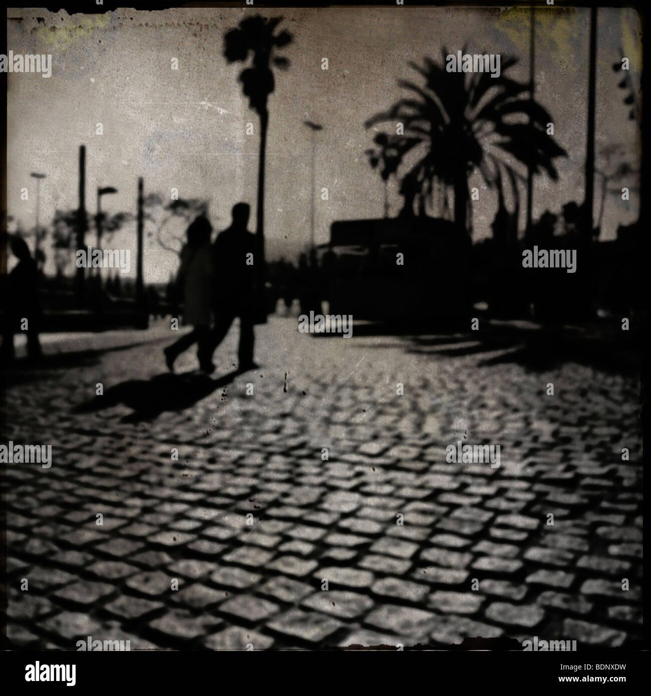 Silhouetten von zwei Menschen zu Fuß auf einer gepflasterten Straße mit Palmen Stockbild