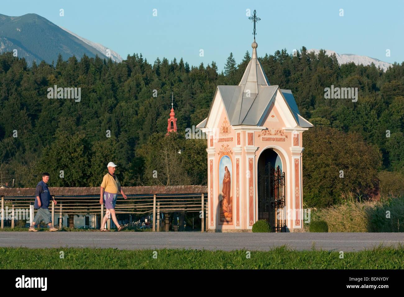 Eine slowenische paar geht vorbei an einer aufwendigen Bildstock in Spodnje Duplje, Slowenien. Stockbild