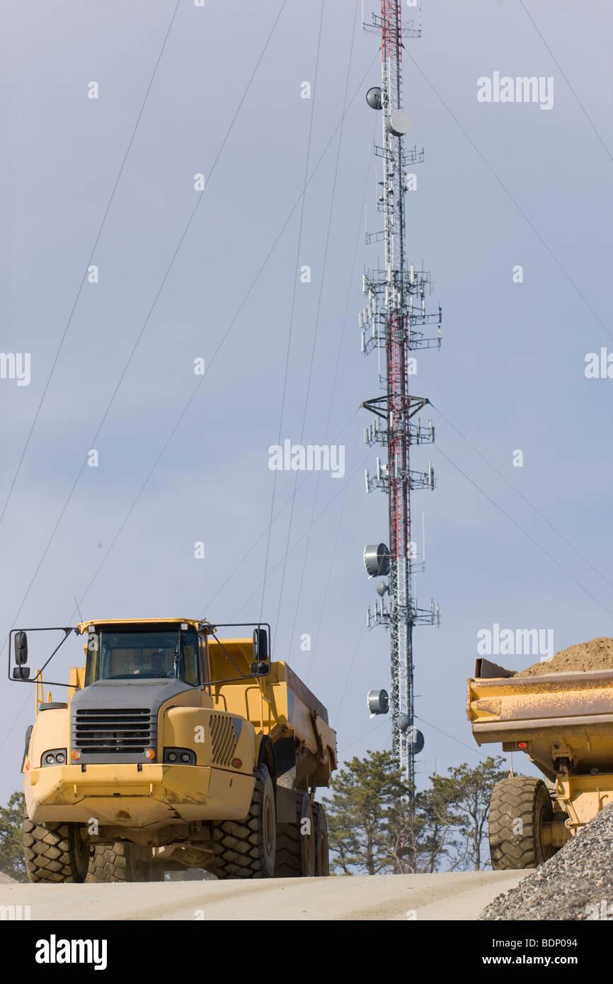 Bagger auf der Baustelle mit einem zellulären Turm im Hintergrund Stockbild
