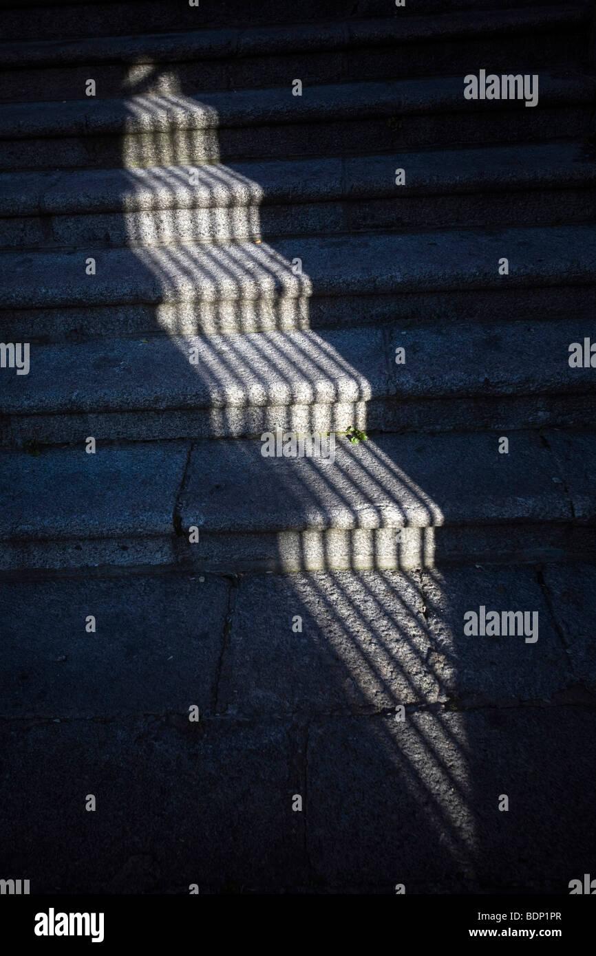 Der Schatten eines Fenster-Gitters auf steinernen Stufen, Caceres, Spanien Stockbild