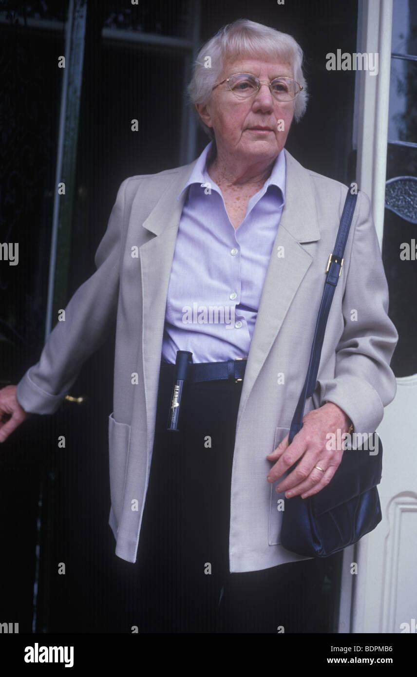 ältere Frau, die das Haus zu verlassen, mit Handtasche und persönlichen Panikalarm Stockbild