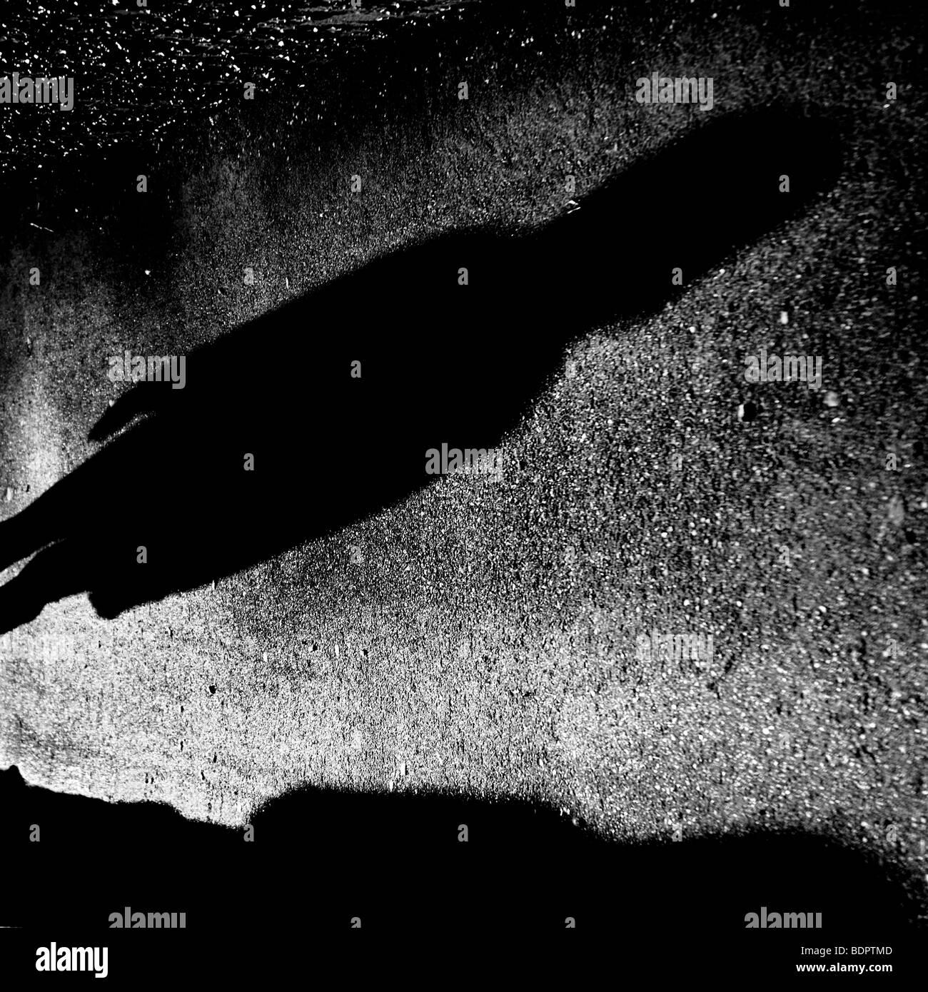 Der lange Schatten einer Figur auf einer Straße Stockbild