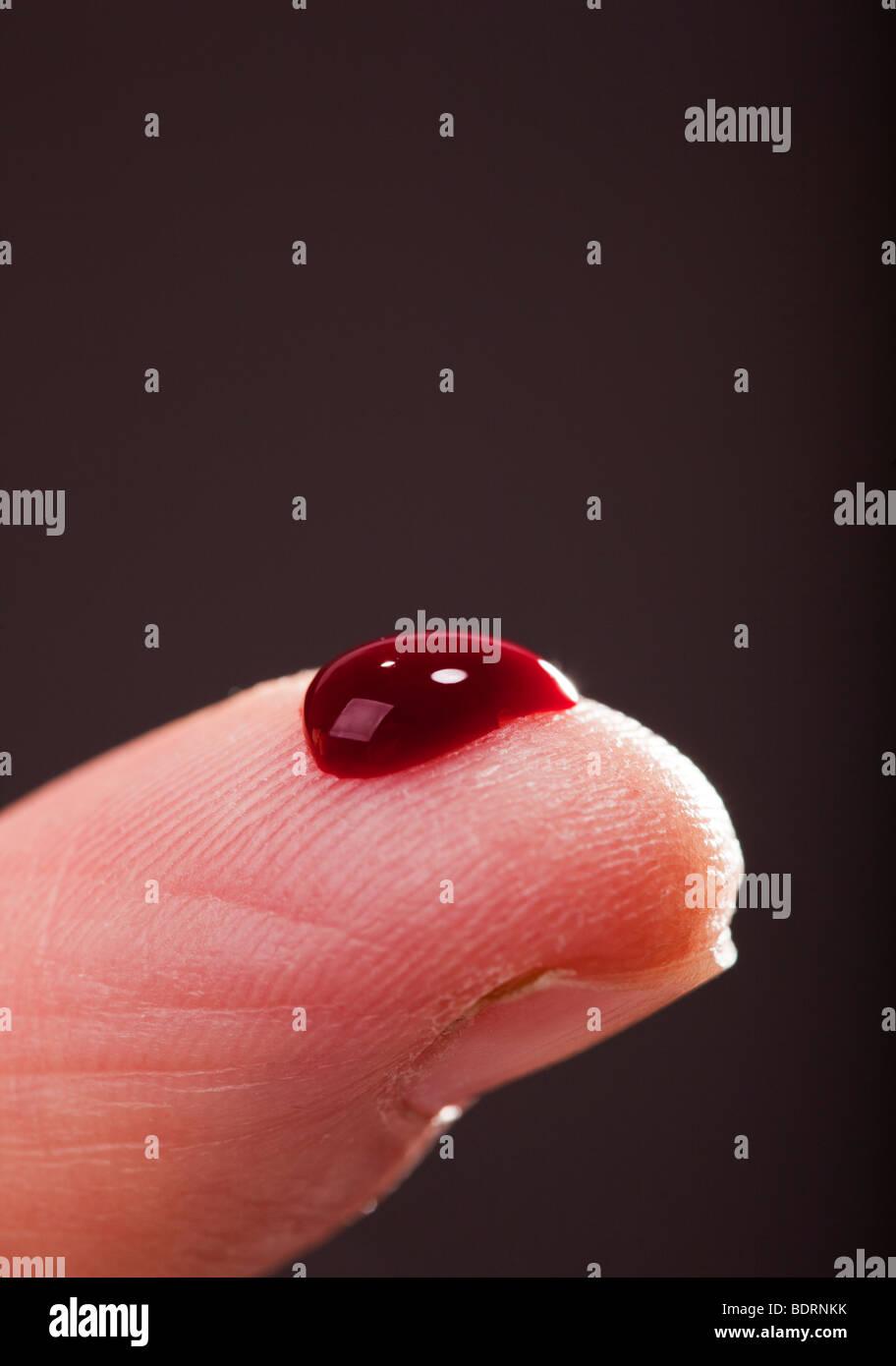 Fingerspitze mit Tropfen Blut. Stockbild