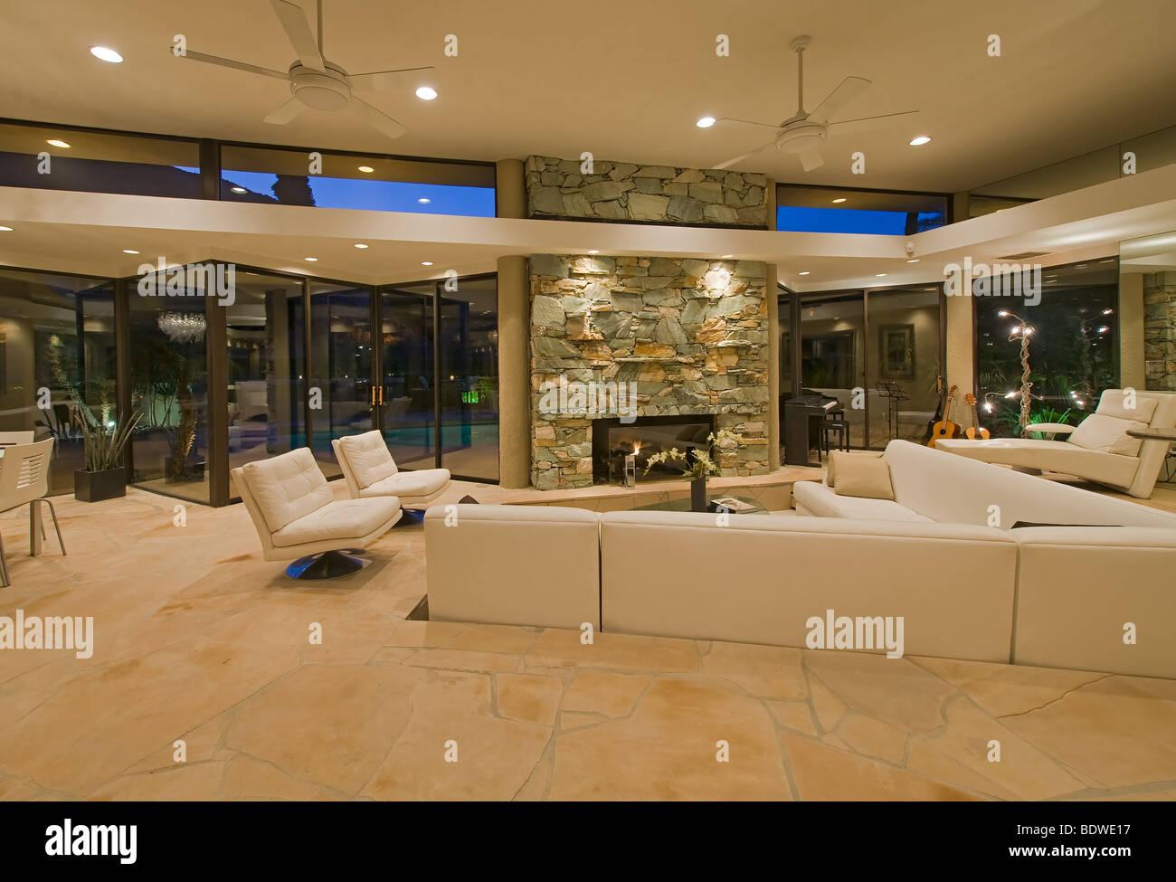 Wohnzimmer mit weißen Schnittsofa, Wände von Glas und Fluss Stein Kamin Stockbild