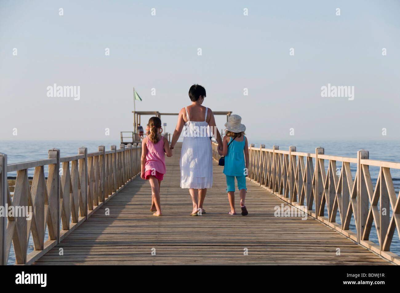 Mutter und zwei Töchter, die zu Fuß auf einem Steg Stockfoto