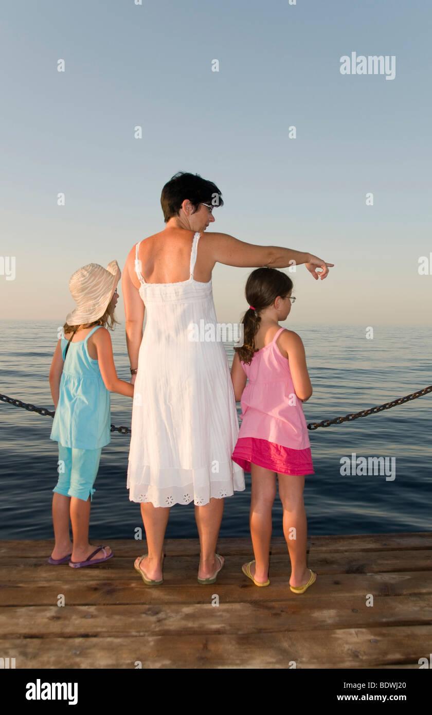 Mutter und zwei Töchter, zeigte auf dem Wasser Stockfoto